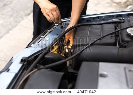 Mechanic testing headlight bulb with electric screwdrivers in a car