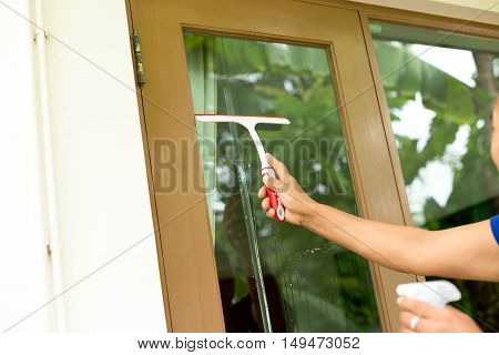 Unidentified woman cleaning windows with spray detergent