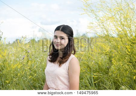 Girl in guipure dress resting on the meadow
