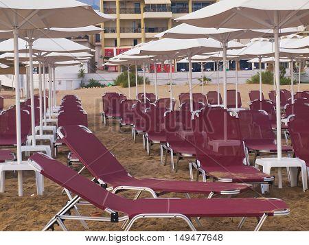 empty beach city Rethymnon Crete sand sun loungers