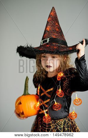 Portrait of the girl of 8-9 years in a suit for Halloween. She represents the evel sorcerer. The girl is dressed in a black-orange dress a hat. In hands at her pumpkin - Halloween symbol.