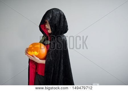 Child is dressed in black -red toga with hood. It is a costume for Halloween. He represents the mysterious wizard. The hood covers the face. Child holds pumpkin with a candle inside - Jack o lantern