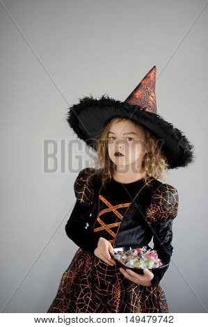 Girl in costume for Halloween. She in image the evil sorcerer. On the girl black-orange dress and a big hat. Girl holds a plate with candies and thoughtfully looks afar. Children adore Halloween.
