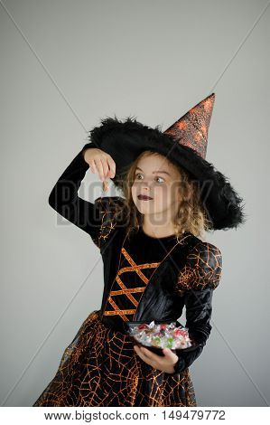 Halloween Party. Girl 8-9 years in image the evil sorcerer. On the girl a black-orange dress and a big hat. Girl holds sweets in hands. She has a ridiculous look. Trick or Treat.