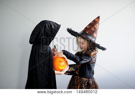 Trick or Treat. Boy and girl in suits for Halloween. They in image powers of darkness. Girl - evil fairy boy - warlock. Girl holds sweets in hands. Boy holds pumpkin - Jack o lantern. Boo