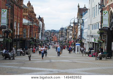 Leeds, United Kingdom - June 24, 2014. Briggate shopping street in Leeds, with historic buildigs, shop windows and people.