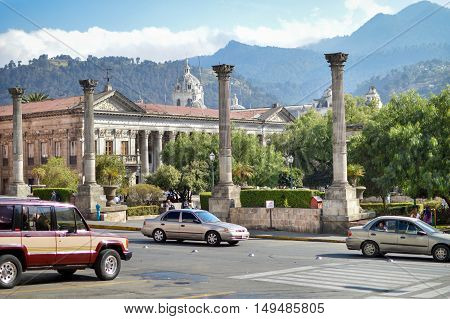 Quetzaltenango, Guatemala - February, 8 2015: Car pass by the central plaza of the historic center of Quetzaltenango, aka Xela, in Guatemala. Municipal palace and mountains seen on the background