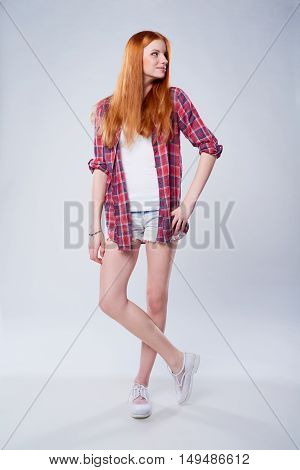 Full length beautiful red haired teen girl in plaid shirt and shorts looking to the side