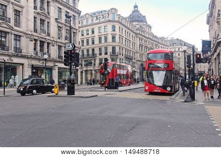 LONDON UK - March 24: Famous Regent Street with busy traffic of public buses and cars while pedestrians walk on the pavement in London UK - March 24 2016; Regent Street is a major shopping street in the West End of London.