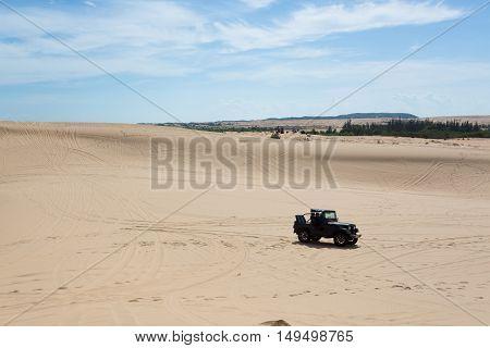 Off Road Car Vehicle In White Sand Dune Desert At Mui Ne, Vietnam