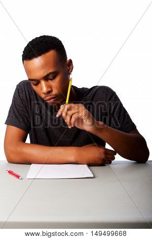 Handsome student thinking concentrating focussing for test examination sitting at desk on white.