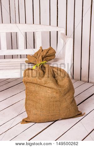 Brown sack on wooden white abstract background