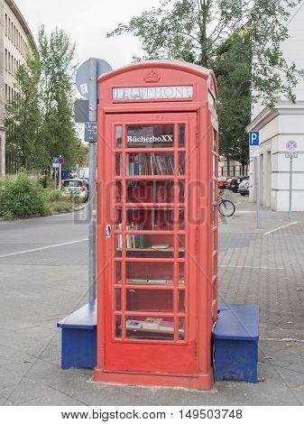 BERLIN GERMANY - SEPTEMBER 29 2016: Buecherboxx red phone box with books inside at Fehrbelliner Platz in Berlin Germany