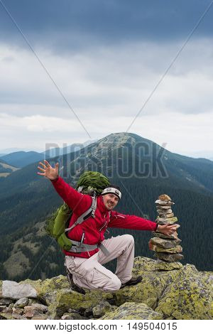 Happy hiker winning reaching life goal success freedom and happiness achievement in mountains. Stack of stones zen. Hiker with backpack on top of a mountain.Concept of success