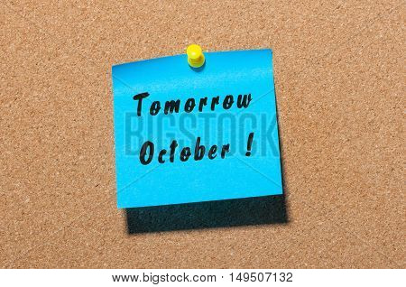 Tomorrow October written on a sticker at notice board with empty space for text.