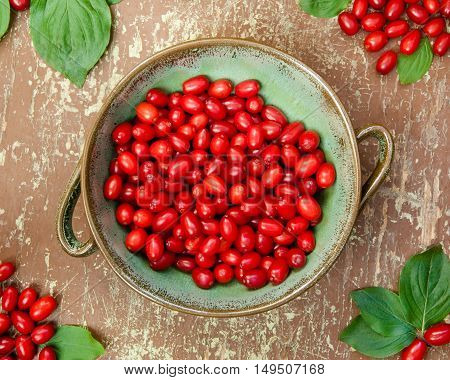 Ripe dogwood berries in a clay bowl on wooden background