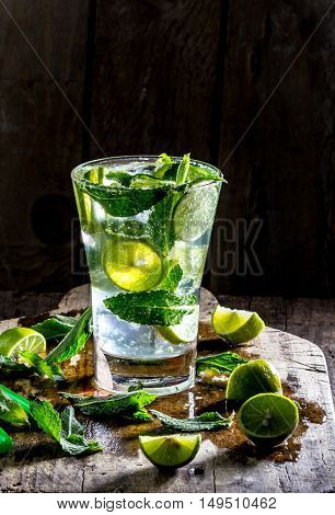 Glass of alcohol cocktail or lemonade. Mohito cocktail with lemon, lime, mint, ise cubes. Cold drink. Fresh lime and mint on wooden background