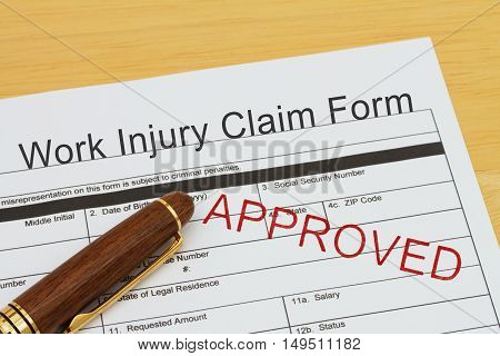 Work Injury Claim Form Approved Work Injury Claim Form with a pen on a desk with an approved stamp
