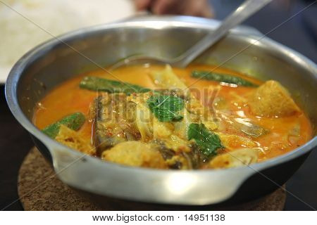 Traditional asian spicy fish curry in metal bowl poster