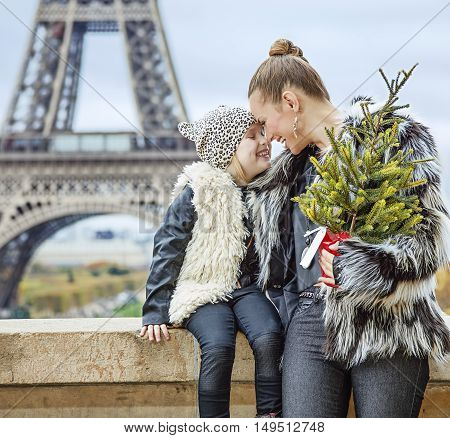 Mother And Daughter With Christmas Tree In Paris Embracing