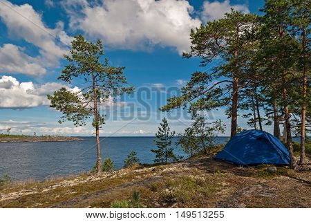 Blue tourist tent on the rocky shore of Lake Ladoga on the background of blue sky with white clouds in Karelia.