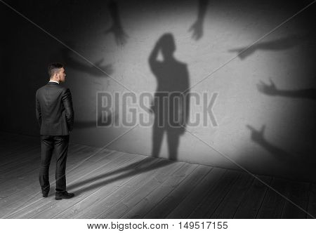 Businessman looking at his shadow where many hands reach for him forcing grab his head. Difficulties at work. Problems and issues. Predicament.