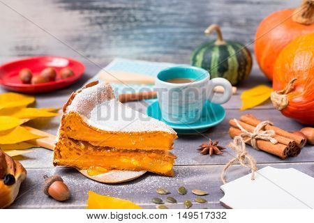 Pumpkin pie dusted with icing sugar with a cup of coffee among the autumn leaves acorns on a wooden surface