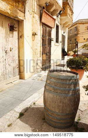 old wooden barrel on narrow street in Malta. Maltese architecture in Mdina, Malta 2013