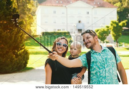 Young Beautiful Family With Cute Toddler Child Making Selfie Photo On Gopro Camera In Park Of Europe