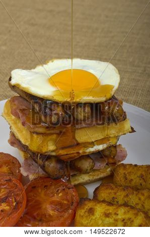 Double Waffle Stack Breakfast Super size Breakfast of waffles, bacon, eggs, sausage in a stack,  a side of tomato, and sunny side up eggs, with hash browns and maple syrup being drizzled over the eggs.