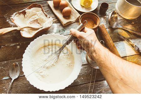 The Chef Knead The Dough With A Whisk. Wheat Flour Batter Eggs A Lemon And Kitchen Utensils On Wooden Table. Preparation Of The Dough In A Rustic Kitchen. Tinted Image