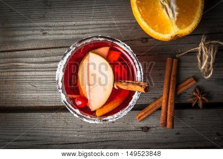 Fragrant autumn and winter sangria with oranges, apples, cranberries and spices, top view, copy space