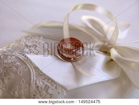 Wedding rings on a white satiny fabric