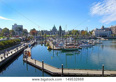Victoria, B.C., Canada - SEPTEMBER 26, 2016: The tourist district Inner Harbor, with Parliament in the background. On a sunny summer day.  Victoria is the Capital city of the Province of British Columbia.