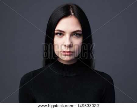 Beautiful serious woman with sad look gray background