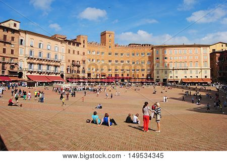Siena, Italy - October 8, 2014. The sloping Piazza del Campo has been Siena's civic and social center since the medieval times. View of Piazza with residential and commercial buildings and people.