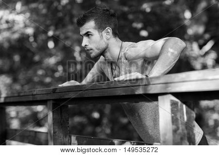 Young sportsman doing push-ups on exercise in park, black and white photo