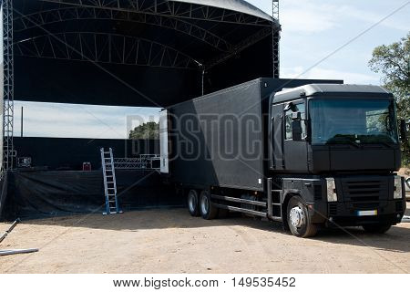 Truck near a concert stage starting setting it up