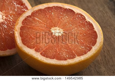 Fresh half pink or rose grapefruit in a close up view on a wooden table showing the juicy tangy pulp and segments