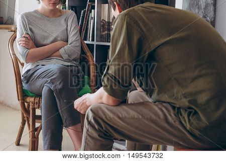 family conflict. Couple discussing sitting near bookshelves. Modern casual hipster look.