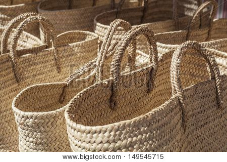 Line of baskets made of cattail fibers at street market stall