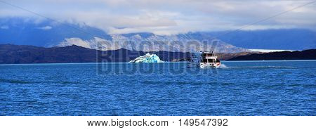Ship and iceberg in a sunny day. El Calafate Patagonia Argentina
