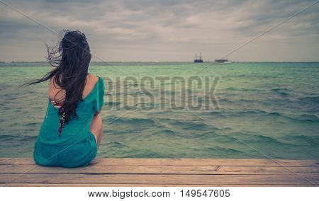 Closeup back view of long hair woman sitting in blue beach dress looking out towards blue ocean and sky. Retro style color tones.