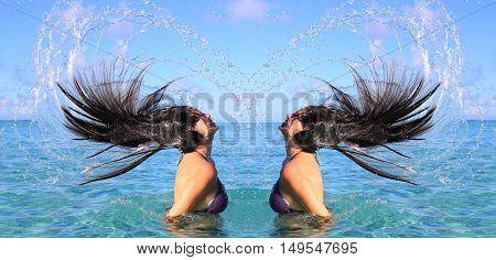 Beauty model girls splashing water with her hair in the ocean. Water splash in heart shape. Mirror scene.