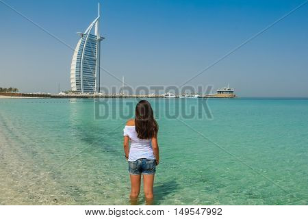 DUBAI UAE - MAY 14 2012: Long hair girl at Jumeirah Beach. In the background the Burj Al Arab Hotel. Repeatedly voted the world's most luxurious hotel.
