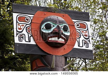Single colourful Totem Pole with large carved face with foliage background in Stanley Park. They are located on the eastern point, just before Hallelujah Point on a bright, sunny spring day.
