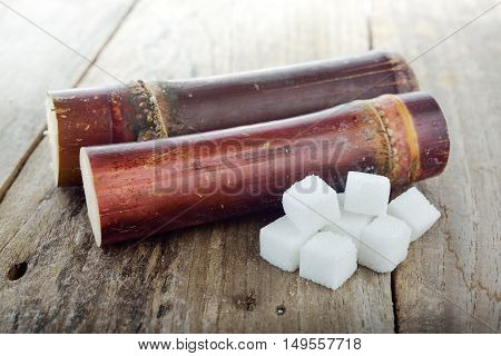 sugar cane and cube sugar on wooden table