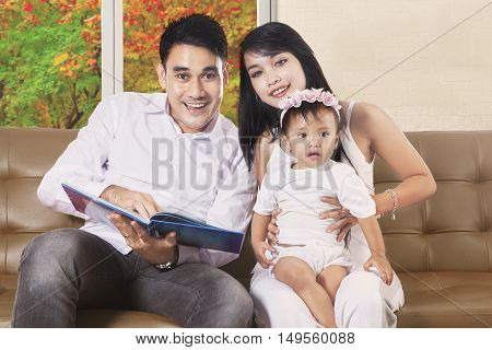 Image of father holding book and daughter sitting with mother on the brown couch while looking at camera autumn on the window