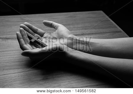 Wooden cross in the hands on wooden table
