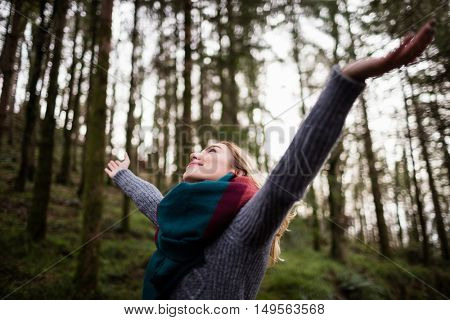 Beautiful woman standing with arms outstretched in forest